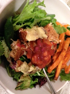 salad with a veggie burger, avocado, salsa, and sweet potato fries