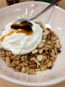 plain greek yogurt, chocolate and caramel sauce, granola, sliced almonds, and mini chocolate chips somewhere under there