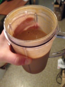 Shake made with a sweet potato, chocolate protein powder, spinach, ice and milk